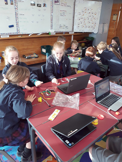 Serena leads younger students Maggie and Ruby in their Makey Makey session.