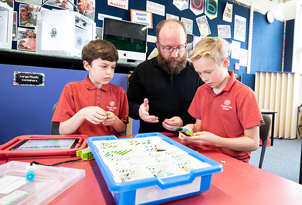 Callum (10), Gareth Sinton,  and Levi (10) use a LEGO WeDo kit to build and code a robot with working arms.