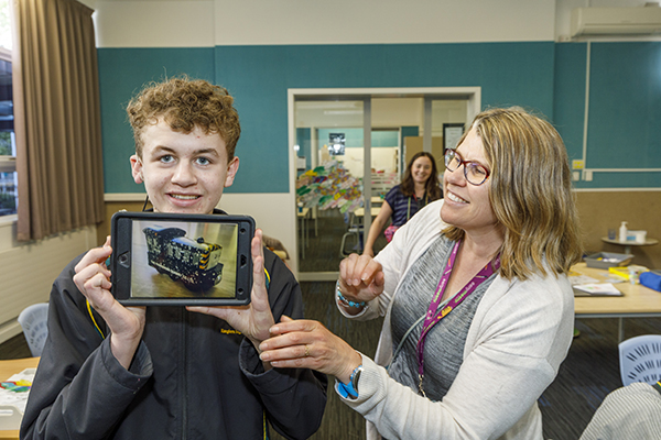 Ben shares his area of special interest with the photographer. Simone Mullan acts as a communication partner for Ben while his  specialist teacher Laura Seddon looks on.