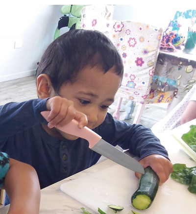 Kind Hands aims to keep the environment and activities as mainstream as possible: Micah (3) enjoys slicing a zucchini.